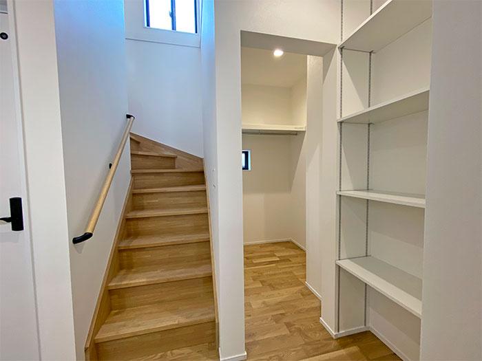階段下にスタイリングエリア。棚とその先には玄関に続く動線