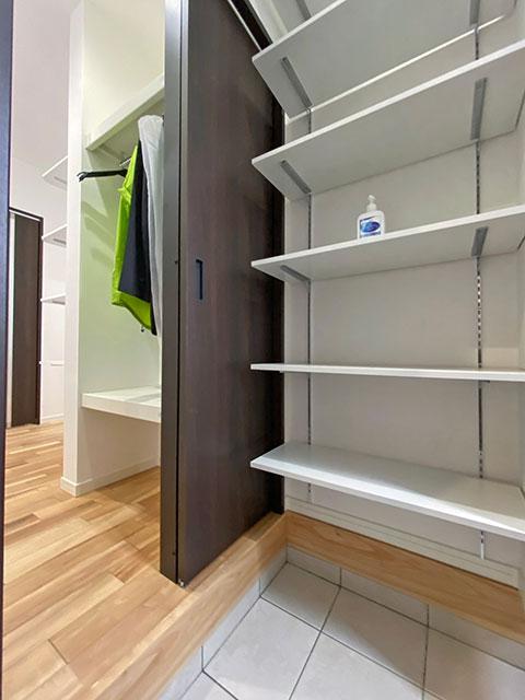 シューズクローゼット<br> 手前にはゴルフバッグやベビーカーが置けます。置いても余裕のある収納スペースになっております。掛ける収納もできるようにハンガーパイプも設置。