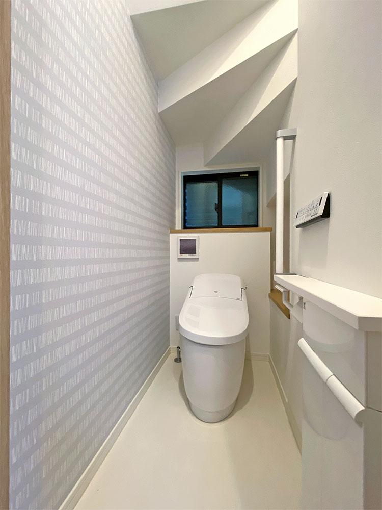 トイレ<br> 階段下のスペースにカウンターを設けたので、トイレットペーパーの収納に使えます。