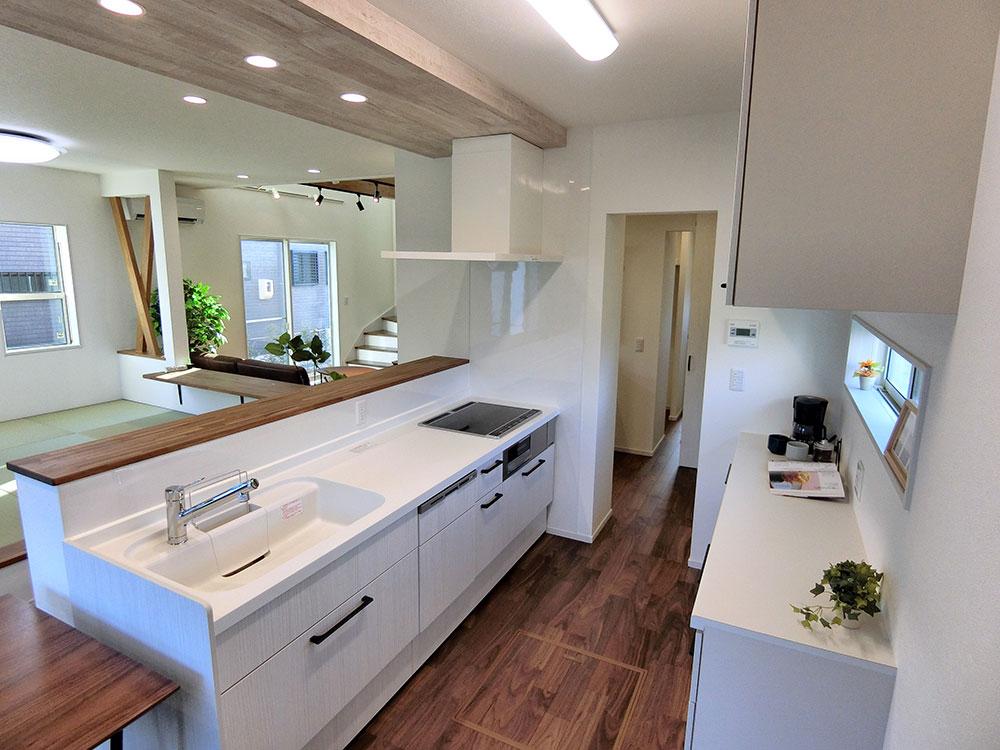 キッチン<br> ダークブラウンの中に映えるホワイトカラーのキッチンを配置しました。
