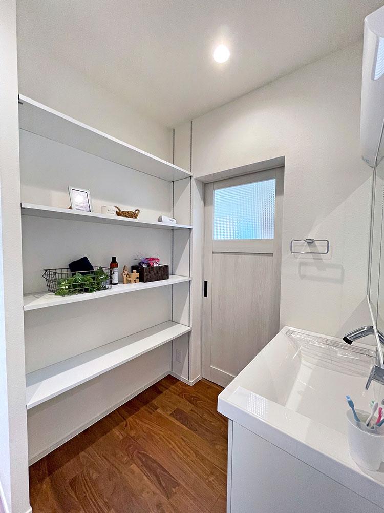 スタイリングエリア<br> 洗面の向かい側には棚収納をつくりました。奥の扉はリビングへ繋がります。