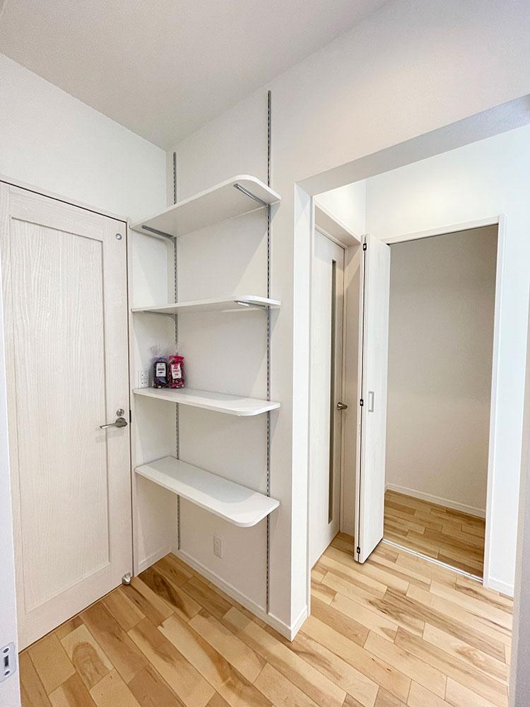 洗面台とトイレの間にある可動棚とリビング収納<br> フェイスタオルやメイク道具、ヘアアイロン、メラミンスポンジなどのお掃除グッズなど置き場にいかがでしょうか?可愛いカゴに入れて収納すればスッキリしそうです♪<br> 右側に見えるのはリビング収納です。
