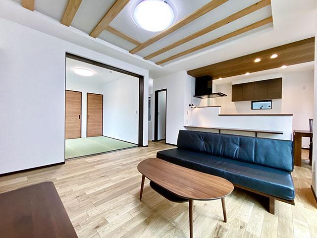 リビング<br> リビングの上部に、柱を挽き割った付梁を使用し木質感を創出したリビング。床にエアーウォッシュ機能を持つナチュラルなフローリングを採用。